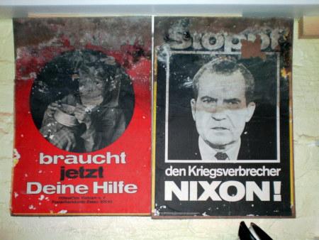 Zwei Plakate aus den frühen Siebziger Jahren, die sich irgendwie bis in die heutige Zeit gerettet haben, zwar verschlissen und angeschimmelt, aber immer noch erkennbar: 'Vietnam braucht jetzt Deine Hilfe' und 'Stoppt den Kriegsverbrecher Nixon'.