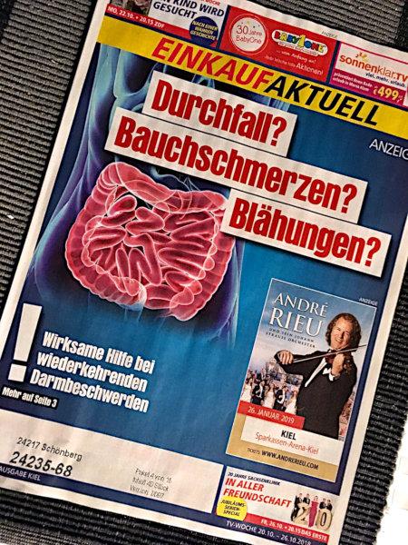 Unbeschreibliches Nebeneinander einer Reklame für ein Quacksalbermedikament gegen Durchfall, Bauchschmerzen und Blähungen und einer anderen Reklame für ein Konzert von André Rieu auf der Titelseite eines Einkauf Aktuell.
