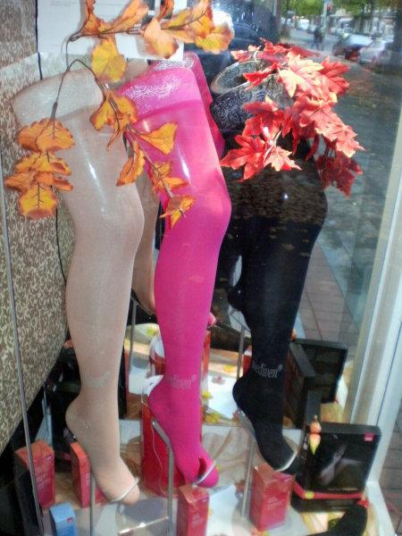 Schaufenster mit drei bunten Beinen, die Strumpfhosen präsentieren, garniert mit buntem Laub