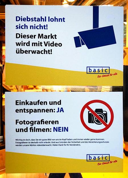 Zwei Aufkleber auf einer Supermarkt-Tür -- Diebstahl lohnt sich nicht! Dieser Markt wird mit Video überwacht! -- Einkaufen und entspannen: Ja. Fotografieren und Filmen: Nein.