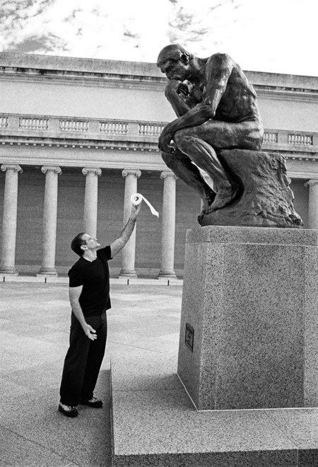 Jemand hält der Skulptur des Denkers eine Rolle Klopapier hin