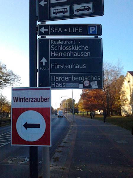 Hinweisschilder zum Großen Garten in Hannover an einem wunderschönen Herbstnachmittag. An den Mast ist ein weiteres Schild angebracht, mit einem Pfeil, der nach links weist. Dieses weitere Schild führt zum 'Winterzauber'.