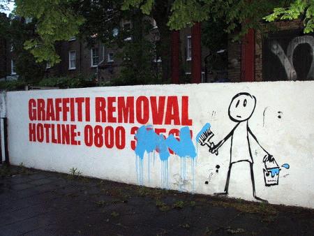 Foto einer Reklame an einer Mauer: Graffiti Removal, gefolgt von einer Telefonnummer. Jemand hat daneben ein Strichmännchen mit blauen Farbeimer und Pinsel an die Wand gemalt, dieses Strichmännchen hat die Telefonnummer mit blauer Farbe durchgestrichen