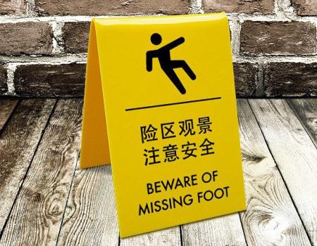 Chinesisches Warnschild mit englischer Übelsetzung des Textes: Beware of missing foot.