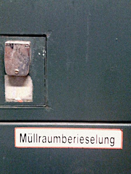 Aufkleber an einer Tür: Müllraumberieselung