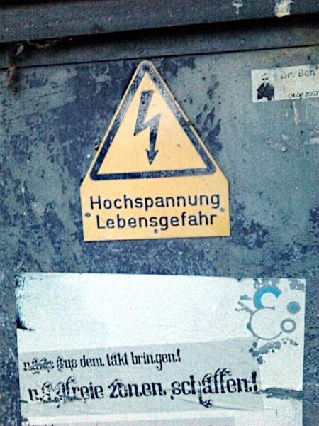 Warnschild: Hochspannung! Lebensgefahr! -- Darunter ein Plakat: Nazis aus dem Takt bringen! Nazifreie Zonen schaffen!
