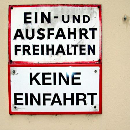 Zwei Schilder untereinander -- Ein- und Ausfahrt freihalten -- Keine Einfahrt.