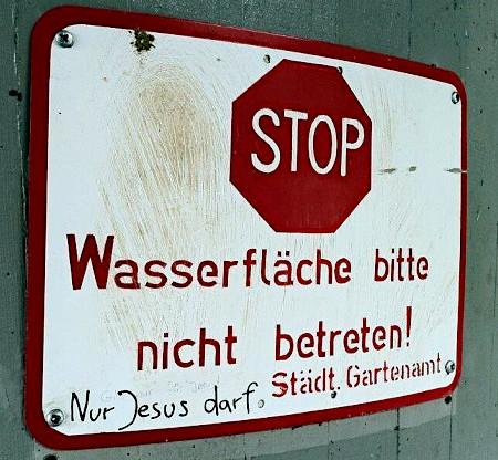 Schild: Stopp! Wasserfläche bitte nicht betreten! Städt. Gartenamt -- Darunter ein Graffito: Nur Jesus darf