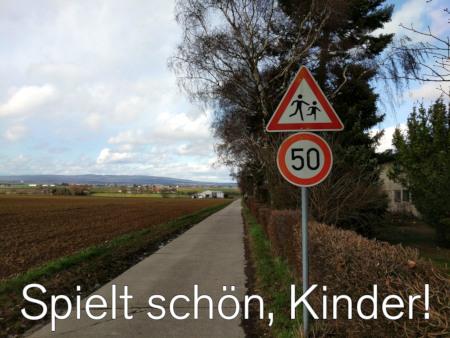 Absurd wirkendes Verkehrszeichen Höchstgeschwindigkeit 50 km/h und spielende Kinder an einem Feldweg