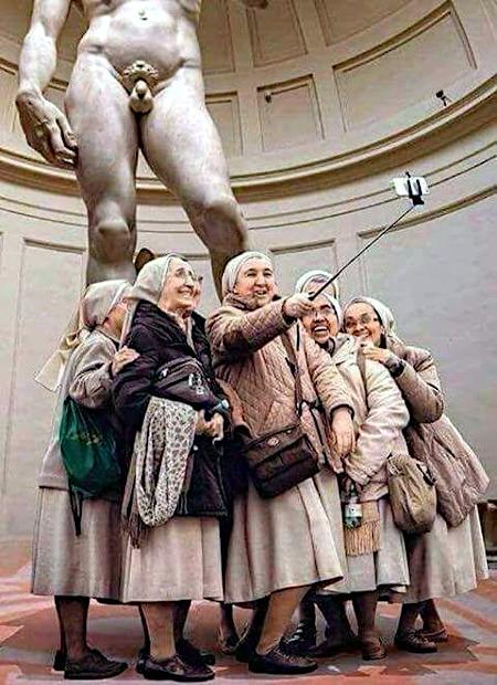 Eine Gruppe alter Frauen macht ein Selfie mit der David-Statue. Von David sind nur die Beine und die Genitalien sichtbar