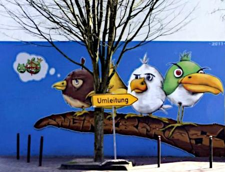 Riesiges Graffito mit drei Vögeln an einer Hauswand, davor steht ein Baum, davor ein Umleitungsschild