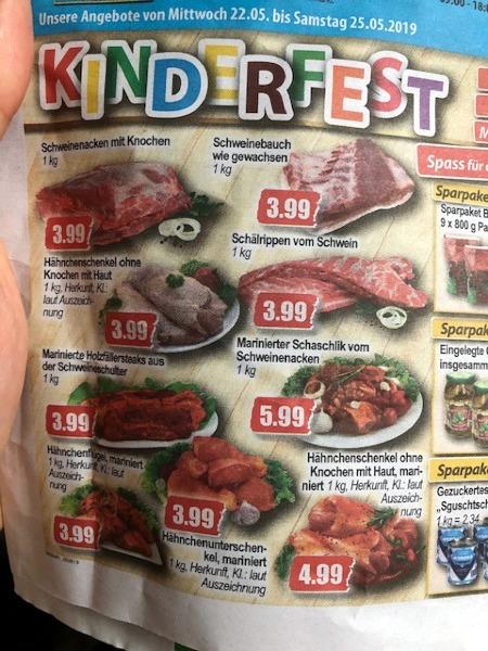 Foto einer Werbung. Die Überschrift ist in bunten Buchstaben 'Kinderfest', darunter die typischen Fotos des Fleischangebotes.
