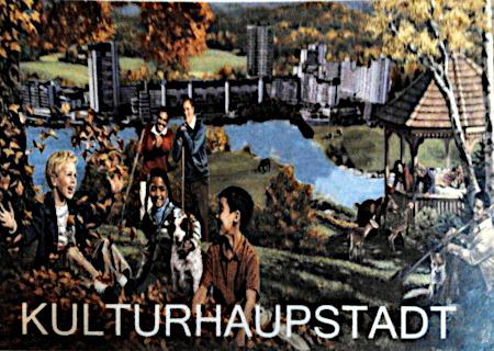 Foto einer Postkarte: Kitschig-idyllische, multikulturelle Szene im Grünen vor einem Fluss, am anderen Flussufer die monströse Betonruine des Ihmezentrums. Darunter das Wort (mit Verschreiber) Kulturhaupstadt.