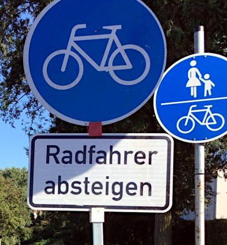 """Verkehrszeichen: Radweg (benutzungspflichtig), darunter ein Zusatzschild """"Radfahrer absteigen"""""""