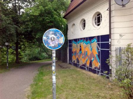 Ein durch Aufkleber völlig unkenntlich gemachtes Verkehrszeichen (Fußweg, Radweg, Gemeinsamer Fuß- und Radweg, Reitweg) an einem Weg.
