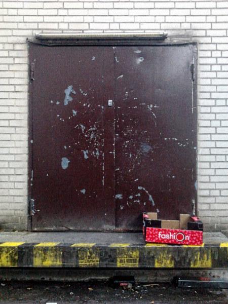 Eine sehr hässliche und dreckige Tür zu einem Lager. An der Tür ein leuchtendroter Pappkarton mit dem Aufdruck 'Fashion'.