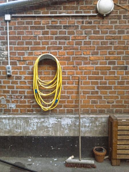 In seiner Wirkung schwierig zu beschreibendes Foto einer Wand, an der eine Lampe angebracht wurde, in der eine Halterung befestigt wurde, an dem ein Gartenschlauch hängt und an der ein Besen lehnt.