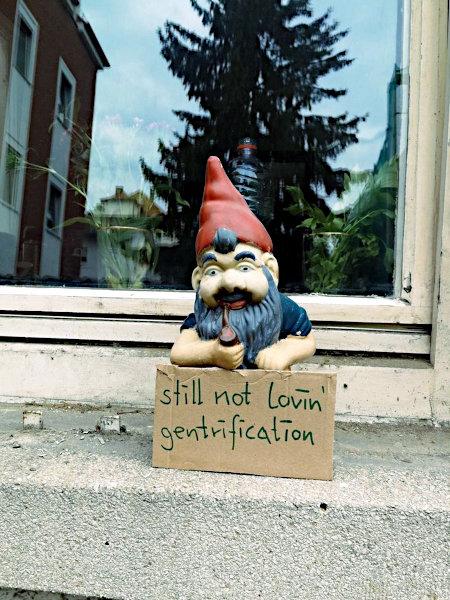 Gartenzwerg in einer Fensterbank, mit Pappschild davor: still not lovin' gentrification'.