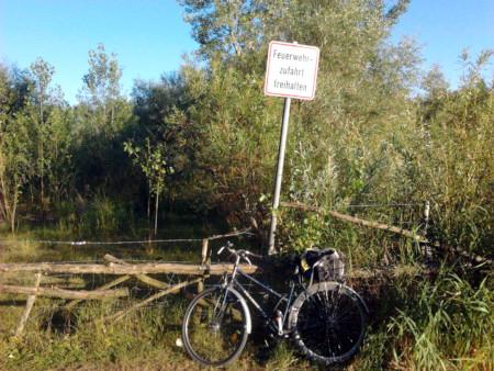 Absurdes Schild 'Feuerwehrzufahrt freihalten' an einem Zaun mit Stacheldraht, hinter dem ein Kiesteich und gut wuchernde Weiden stehen