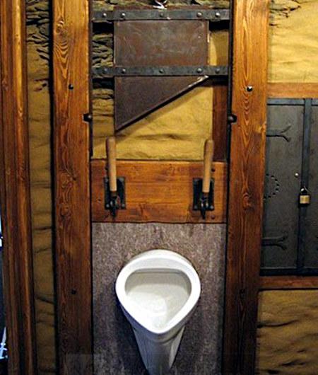 Ein Urinal, an dem eine Guillotine befestigt ist, die den Penis abtrennt