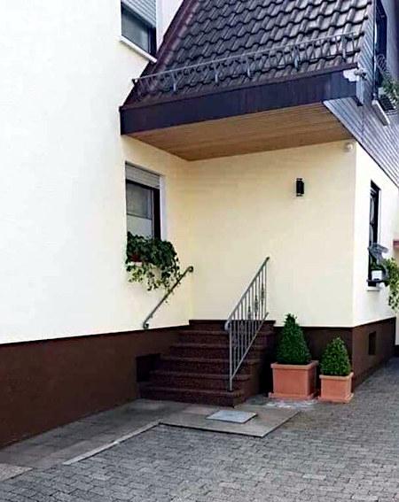 Unbeschreibliches Foto eines Hauses, dessen Treppe an der Wand endet.