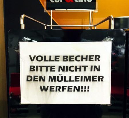 Aushang an einem Kaffeeausschank: Volle Becher bitte nicht in den Mülleimer werfen!!!