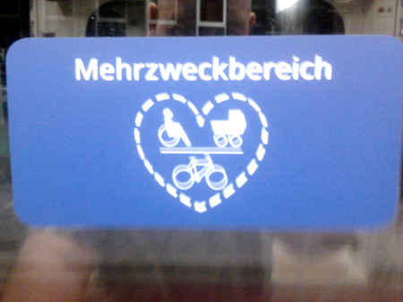Absurd-dadaistisch anmutender Aufkleber in Straßenbahnen des hannoverschen Nahverkehrsbetreibers üstra -- Unter dem Wort 'Mehrzweckbereich' ein Herz in gestrichelten Linien, in dem ein Piktogramm für einen Rollstuhlfahrer, ein Piktogramm für einen Kinderwagen und ein Piktogramm für ein Fahrrad platziert wurde.