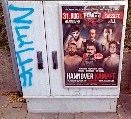 Foto eines Telefonverteilerkastens mit Werbeplakat für eine Kickboxing-Veranstaltung in Hannover und dem großen Werbespruch 'Hannover kämpft'. Links daneben ist ein Graffito mit dem Wort 'Zeck'.