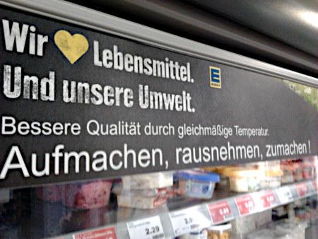 Aufkleber auf einem Kühlschrank in einem Edeka-Markt: Wir ❤️ Lebensmittel. Und unsere Umwelt. Bessere Qualität durch gleichmäßige Temperatur. Aufmachen, rausnehmen, zumachen!