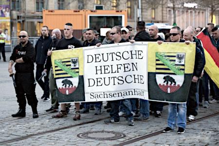 Eine Gruppe von Neonazis trägt ein Transparent 'Deutsche helfen Deutsche Sachsen-Anhalt'