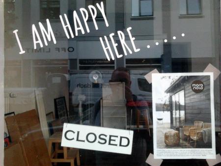 Fenster einer insolventen Kneipe mit Reklame 'I am happy here', darunter das Schild 'Closed'.