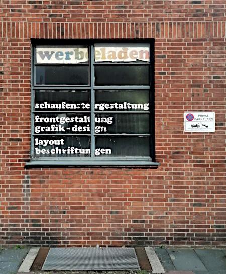 Schäbig beklebtes Fenster in einem Industriegebiet: werbeladen -- schaufenstergestaltung -- frontgestaltung -- grafik-design -- layout -- beschriftungen