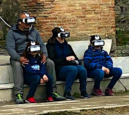Foto eines Erwachsenen mit drei Kindern, die zusammen draußen sitzen, jeder mit einer Virtual-Reality-Brille auf den Augen