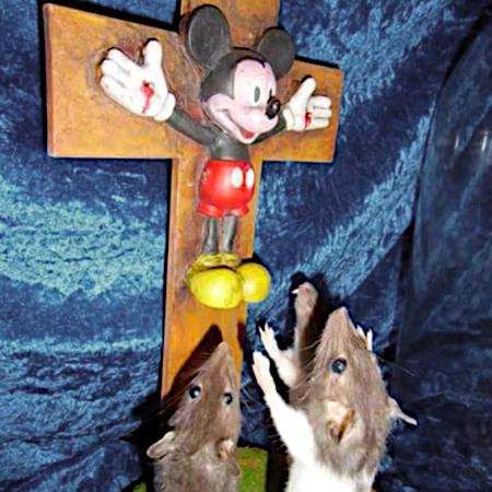 Micky Maus an einem Kruzifix, davor drei Mäuse in einer Haltung, die an Anbetung erinnert.