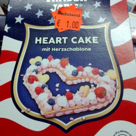 Produktverpackung: Heart Cake. Mit Herzschablone. Aufgeklebtes grelloranges Preisschild: Reduziert, 1€.