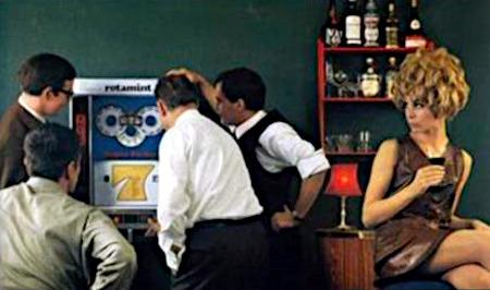 Detail aus einer anderen Reklame für das NSM-Geldspielgerät Rotamint Super Sieben aus dem Jahr 1968: Vier Männer stehen in Kneipenatmosphäre vor einer Rotamint Super Sieben und beachten die aufreizend gekleidete, gelangweilt herumsitzende Frau nicht.