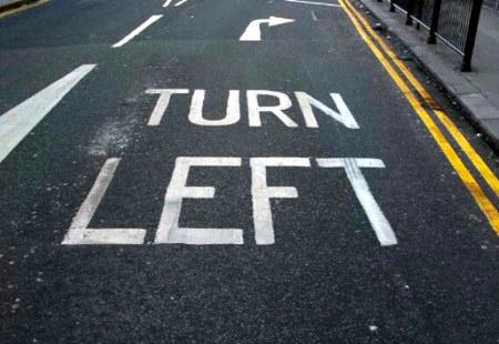 Straßenmarkierung mit einem Pfeil, der nach rechts weist. Dazu Text auf der Fahrbahn: 'Turn Left'.