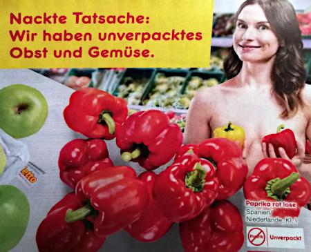 Reklame an der Gemüsetheke eines Netto-Marktes -- Eine breit lächelnde, nackte Frau hält sich zwei Paprika als Sichtschutz vor die Brüste -- Nackte Tatsache: Wir haben unverpacktes Obst und Gemüse
