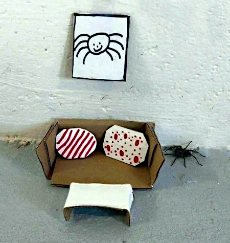 Kaum beschreibliches Foto. Einer großen Spinne wurde mit Teilen aus Pappkarton eine wohnliche Ecke am Boden eingerichtet.