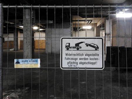 Von einer Fa. Kurt König aufgestellter Bauzaun im Sockelgeschoss der Ruine des brutalistischen Ihmezentrums mit obskurem Parkverbotsschild