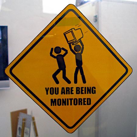 Schild im Stile eines US-amerikanischen Verkehrszeichens mit einer Warnung. Ein Strichmännchen verfolgt mit erhobenem, zum Wurfe angesetzten Monitor ein anderes Strichmännchen. Darunter der Text: You are being monitored