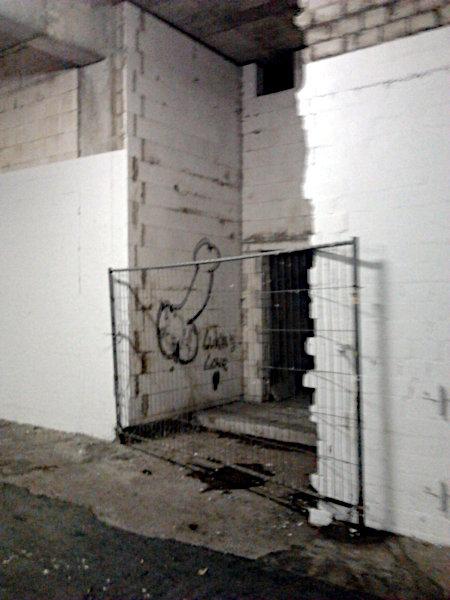 Ein hässlicher Gang im Ihmezentrum in Hannover-Linden. In einer dunklen Nische ein Graffito mit einem erigierten Penis, dazu der Text 'was love'. Vor diesem Werk eines unbekannten Künstlers eine Absperrung durch ein Absperrgitter.