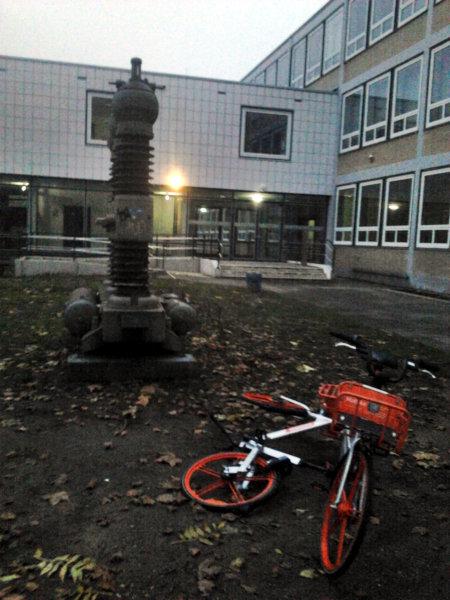 Schwierig zu beschreibenes Foto einer Berufsschule für Elektrotechnik. Vor der Schule steht ein riesiger Isolator für Starkstrom. Vor dem Isolator liegt ein oranges Leihfahrrad wie achtlos hingeworfen.