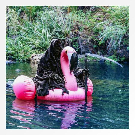 In seiner Wirkung kaum beschreibbares Foto eines schwarz gewandeten Mannes mit Sense und dunkler Skelettmaske, der auf einem quietschpinkfarbenen aufblasbaren Flamingo im Wasser dümpelt