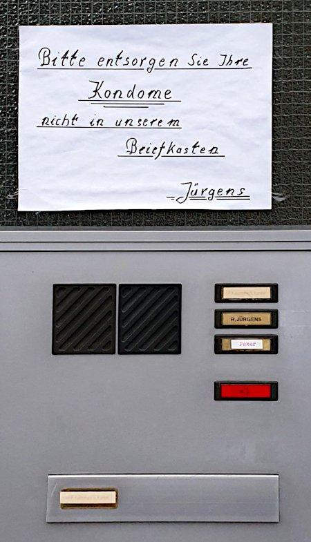 Handgeschriebener, angeklebter Zettel über den Briefkästen eines Wohnhauses: Bitte entsorgen Sie Ihre Kondome nicht in unserem Briefkasten -- Jürgens