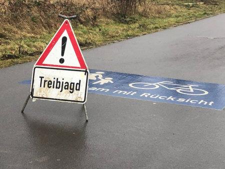 Foto eines Weges, der durch Straßenmarkierungen als geteilter Rad- und Fußweg ausgezeichnet ist, mit der Aufforderung zur Rücksichtnahme. Auf diesem Weg steht ein provisorisches Warnschild: Treibjagd