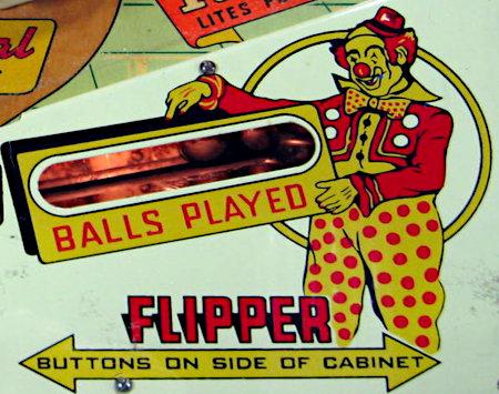 Detail aus dem Gottlieb-Flipper Ace High aus dem Jahr 1957: Ein Clown zeigt auf das Fenster, in dem die bereits gespielten Kugeln sichtbar sind, darunter steht: Balls Played