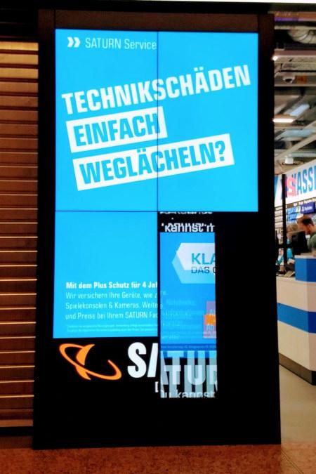 Ein kaputtes Reklamedisplay bei Saturn Hansa zeigt den Reklametext 'Technikschäden einfach weglächeln. Saturn Hansa'.