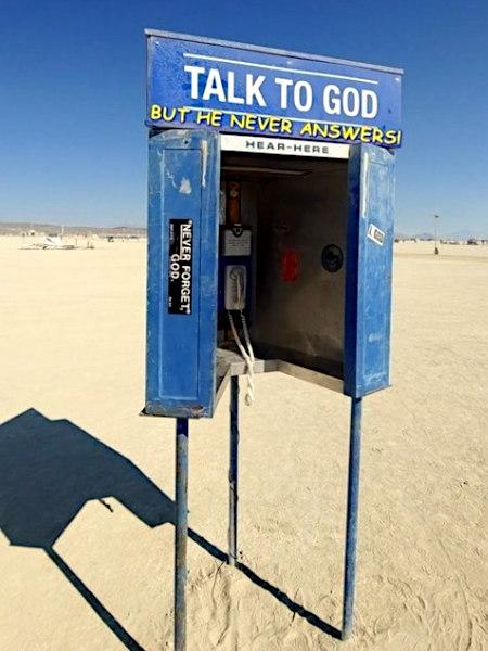 Unbeschreibliches Foto einer nicht angeschlossenen Telefonkabine in der Wüste, über der die Worte 'Talk to God' stehen. Jemand hat daruntergeschrieben: 'but he never answers!'.