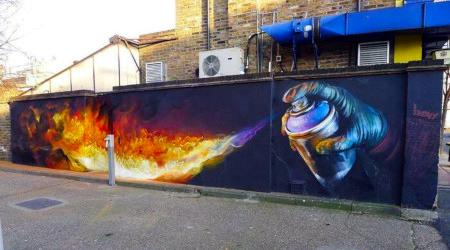 Foto einer Mauer mit einem Graffito. Das Graffito zeigt eine Hand mit einer Spraydose, aus der Flammen schießen, die über die ganze Wand gehen